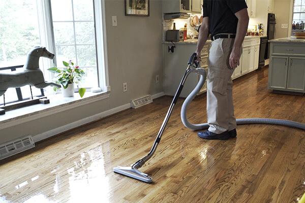 Stanley Steemer technician professionally cleaning hardwood floor