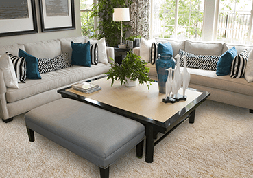 Clean, light room with two white couches, and a coffee table