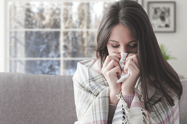 Women blowing her nose in the cold, winter