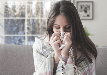 Women blowing her nose into a tissue during the winter