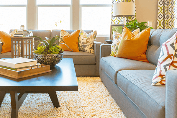 Living Room with warm hues showing the couches, coffee table, and window