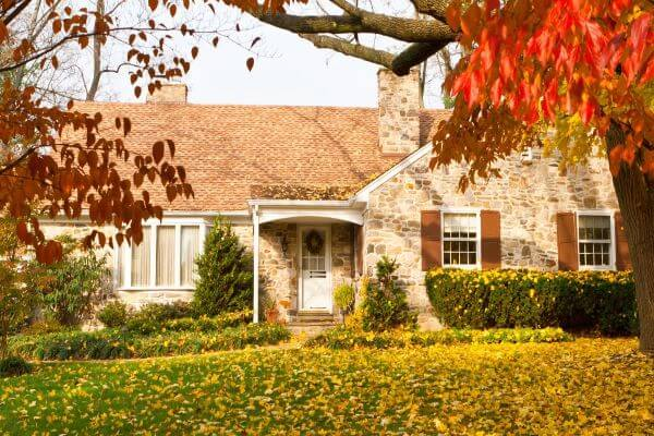 Stone house surrounded by yellow, red, and brown leaves
