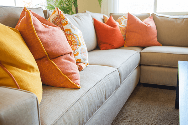 Gray fabric sectional with yellow and orange throw pillows