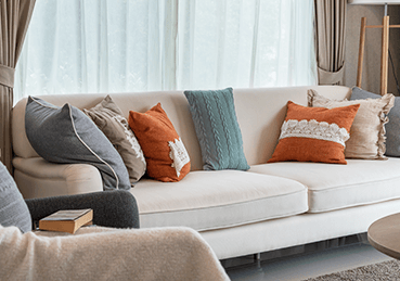 Fabric beigh couch with orange and yellow pillows