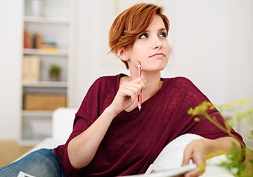 Woman sitting with a pen on her couch pondering a question.