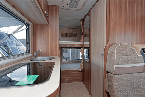 RV living space showing the kitchenette to the side and seating. Wood paneling are the walls.