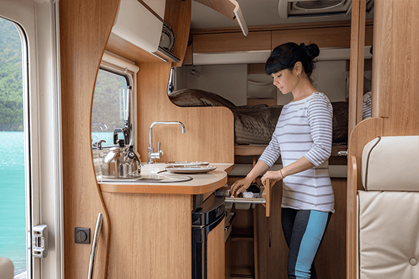 Woman opening a drawer in a small RV kitchenette