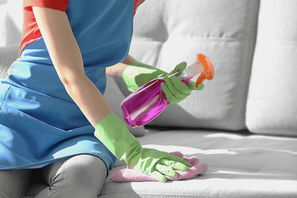 Woman with rubber gloves and apron on spot cleaning a couch