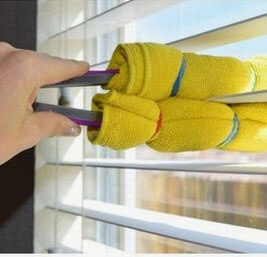 Hand cleaning blinds with a towel wrapped around kitchen tongs.