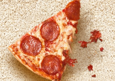 Pizza slice sitting on carpet with sauce stains.