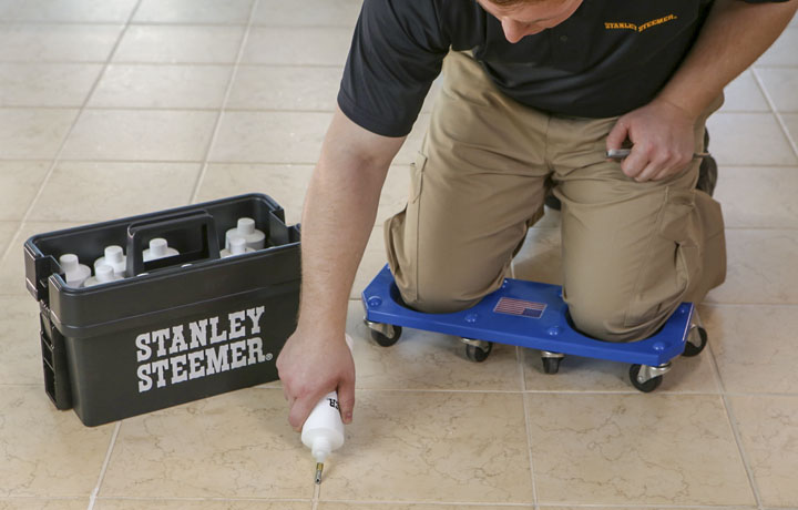 Stanley Steemer technician sealing the grout lines on a tile floor.