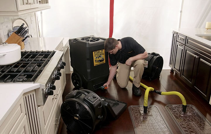 Stanley Steemer technician setting up water damage restoration equipment in a customer's kitchen.